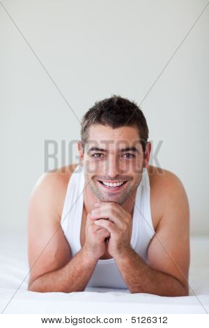 Attractive Man Lying In Bed Smiling
