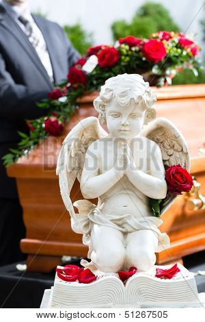 Mourning man on funeral with red rose standing at casket or coffin