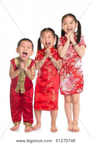Group of oriental children wishing you a happy Chinese New Year, with traditional Cheongsam full length standing isolated on white background.