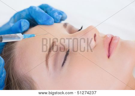 Surgeon in bright operating room making injection on woman's forehead