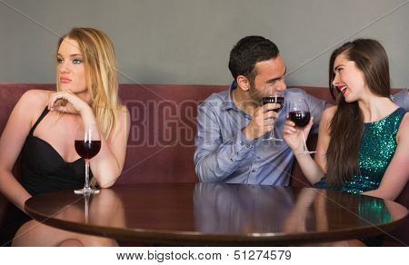 Blonde woman feeling alone as two people are flirting beside her in a nightclub