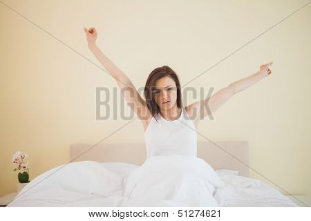 Awakened brunette stretching in her bed in a bedroom on yellow background