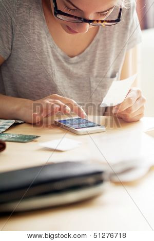 Woman is counting money on her phone while holding a cheque. There is also a leather wallet close to the camera