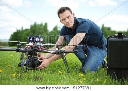 Portrait of confident young engineer setting camera on photography drone in park