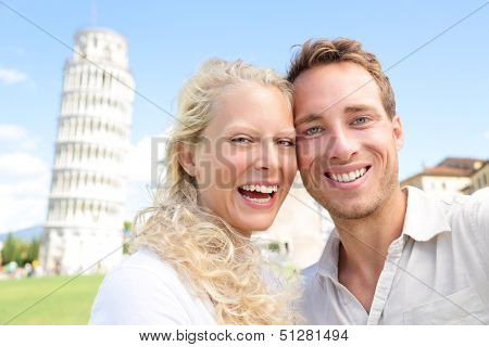 Young couple happy having fun on travel to Pisa. Tourists traveling visiting The Leaning Tower of Pisa. Beautiful laughing couple in love on romantic holidays vacation. Tower of Pisa, Tuscany, Italy.