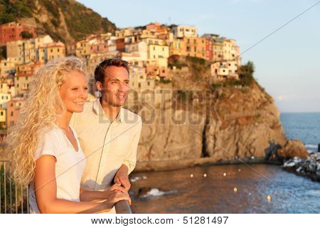 Romantic couple in love by sunset on holidays travel. Young beautiful couple enjoying ocean view romance. Young people, man and woman traveling on vacation in Manarola, Cinque Terre, Liguria, Italy