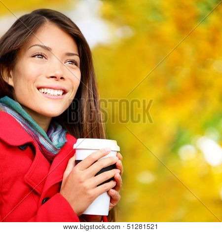 Coffee woman drinking coffee outside in fall forest. Beautiful young woman drinking hot drink from disposable paper cup outdoors in pretty autumn foliage. Multicultural Caucasian / Asian female model.