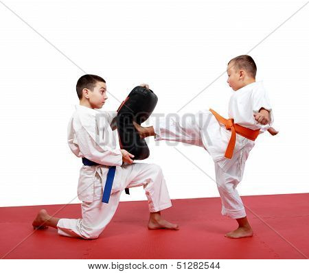 Boy in a kimono hits foot the kick simulator which in the hands of the other sportsman