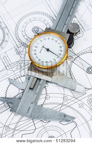 Metal vernier caliper on technical drawing