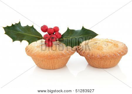 Mince pie cakes with snowflake design, holly and red berry leaf sprig over white background