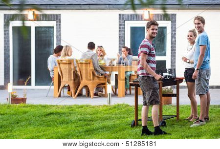 Group of a young friends preparing a barbecue in a back yard
