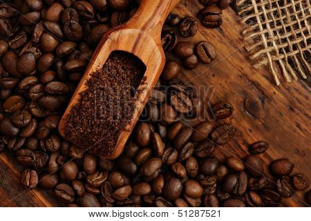 Olive wood measuring scoop with coffee beans, ground coffee and burlap on rustic dark wood background.  Low key still life with directional, natural lighting.
