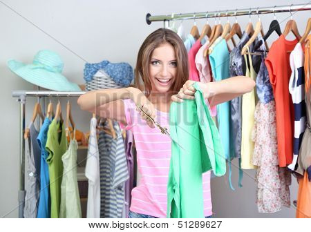 Beautiful girl throws out unnecessary clothes in room
