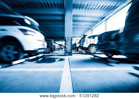 Parking garage, interior with a few parked cars,Motion blur