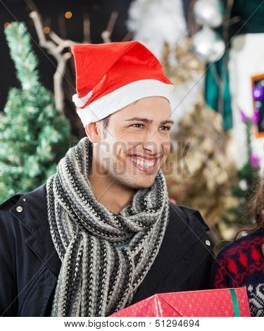 Handsome young man with Christmas present smiling in store