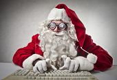 stock photo of ironic  - nerd Santa Claus writes with keyboard - JPG