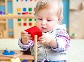 stock photo of montessori school  - cute little girl in the classroom early development plays with bright toys - JPG