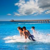 Teenager surfers surfing running jumping on surfboards at Newport pier beach California [photo-illus