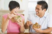 stock photo of chinese food  - Couple Eating Food Healthy Eating Home Cooking mealmealtime 30s Asian Casual Clothing Chinese Chopsticks Color Colour Dining Room Domestic Life Enjoying Happy Holding Home Horizontal Husband Image Indoors Inside Looking At Camera Looking At Each Other Man - JPG