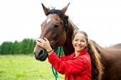 stock photo of brown horse  - Beautiful smiling girl with her brown horse outdoors - JPG