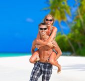 stock photo of piggyback ride  - Happy young couple having fun on tropical beach  - JPG
