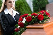 stock photo of casket  - Mourning woman on funeral with red rose standing at casket or coffin - JPG