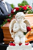 stock photo of casket  - Mourning man on funeral with red rose standing at casket or coffin - JPG