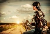 stock photo of jacket  - Biker girl in a leather jacket on a motorcycle looking at the sunset - JPG