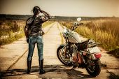 picture of biker  - Biker girl stands on the road and looks into the distance - JPG
