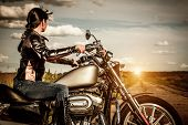 stock photo of motorcycle  - Biker girl in a leather jacket on a motorcycle looking at the sunset - JPG