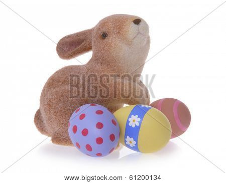 Easter rabbit toy with three painted eggs on white background