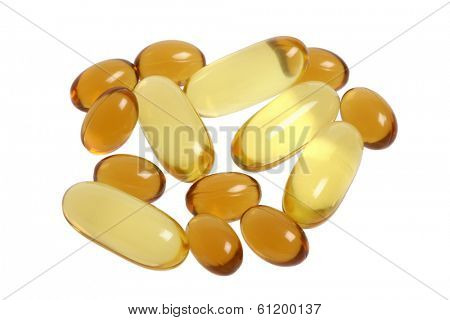 Large and small yellow vitamin pills on white background