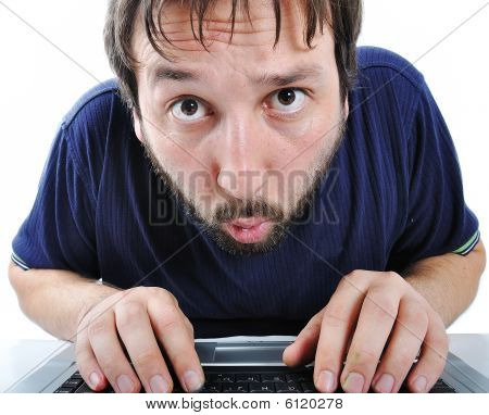 Young Man With Beard And Expression On His Face In Front Of Laptop