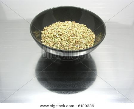 Black Bowl Of Chinaware With Buckwheat On Reflecting Surface