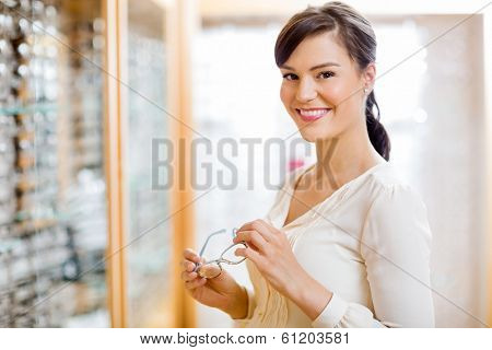 Portrait of happy young woman buying glasses in optician store