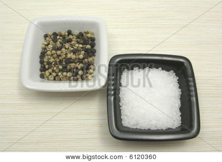 Bowls Of Chinaware With Peppercorns And Salt On Beige Underlay