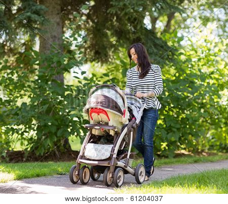 Happy young woman pushing baby carriage in park