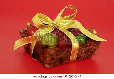 fruitcake with bow on red background