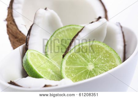 Coconuts and lime in white bowl