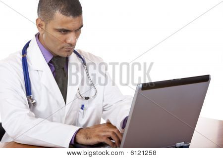 Medical Doctor Reviewing His Notes On Laptop