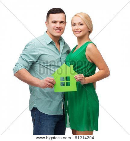 real estate, family and couple concept - smiling couple holding green paper house