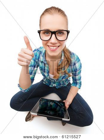happiness, technology, internet and people concept - smiling young woman sitiing on floor with tablet pc and showing thumbs up