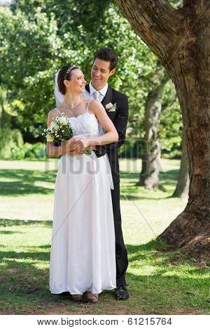 Full length of newly wed couple looking at each other while standing in park
