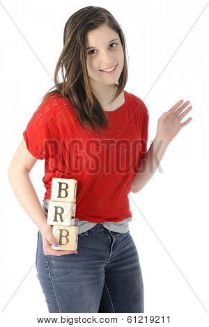 A pretty young teen happily waving as she hold rustic alphabet blocks with the letters she uses on her phone:  BRB, standing for