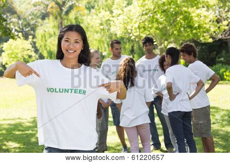 Portrait of beautiful volunteer pointing at tshirt with friends in background