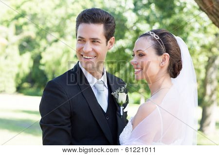Happy young newly wed couple looking away in garden