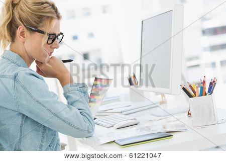 Blonde focused designer working at her desk in creative office