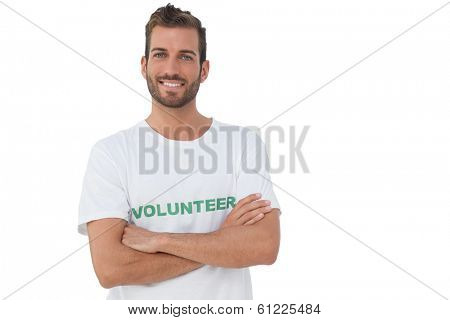 Portrait of a happy male volunteer standing with hands crossed over white background