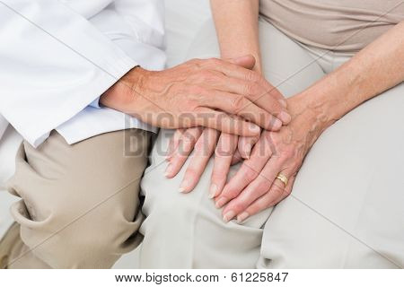 Close-up mid section of a female senior patient visiting a doctor at the medical office
