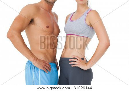 Mid section of a fit young couple standing over white background